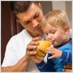 Caucasian father helping toddler son drink orange juice.